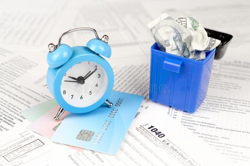 1040 tax form with blue alarm clock on credit cards and crumpled hundred dollar bill in trash bin. 1040 Individual income tax return form with blue alarm clock royalty free stock image