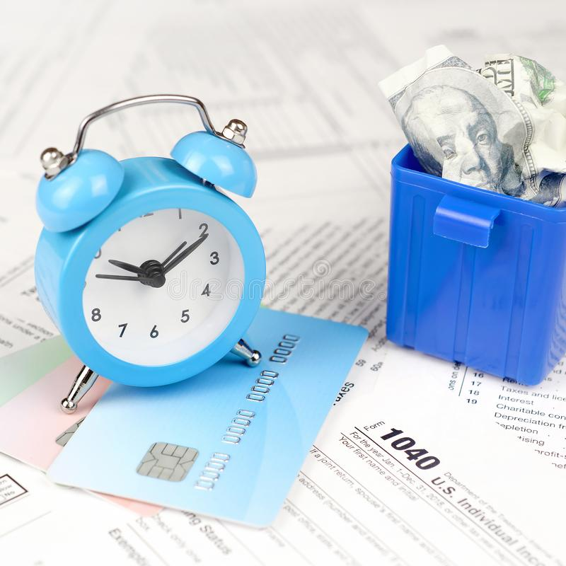 1040 tax form with blue alarm clock on credit cards and crumpled hundred dollar bill in trash bin. 1040 Individual income tax return form with blue alarm clock stock image