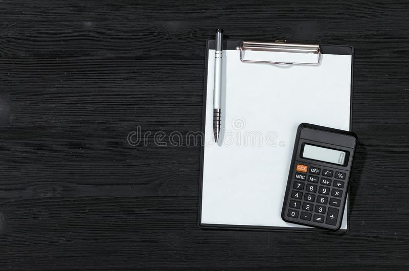 Tax form. Tax calculation mock up. Payment on account. Blank document page and calculator on the black table background stock image