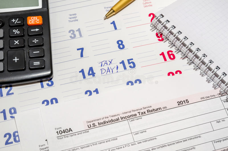 Tax form with calculator, pen, notepad above paper calendar. Us tax form with calculator, pen, notepad above paper calendar royalty free stock photo