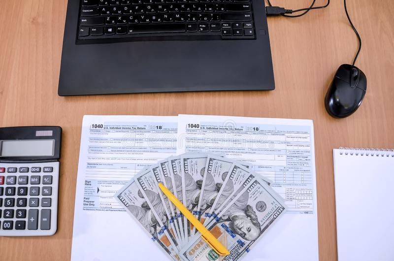 Tax form 1040, dollars, calculator, laptop, notebook and pen on a wooden, office desk stock images