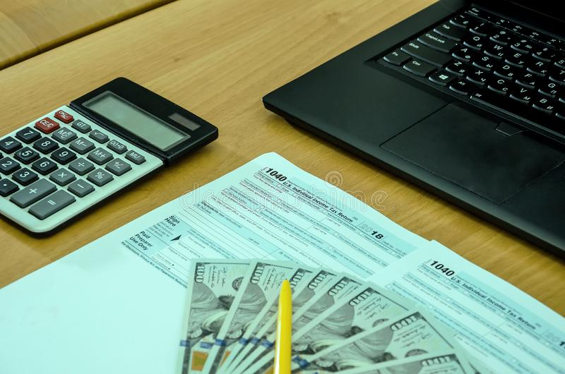 Tax form 1040, dollars, calculator, laptop, notebook and pen on a wooden, office desk royalty free stock photo
