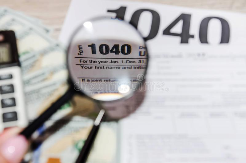 Tax form 1040, dollars, pen and magnifier on a gray, wooden table. Tax form 1040, dollars, pen and magnifier on a wooden table royalty free stock photo