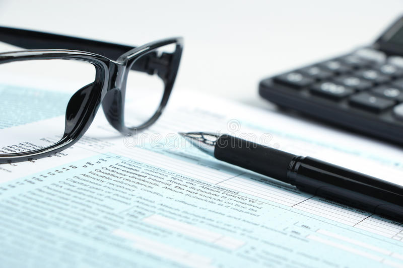 Tax form financial concept. Tax form business financial concept with a pen, a pair of glasses and a calculator aside royalty free stock images