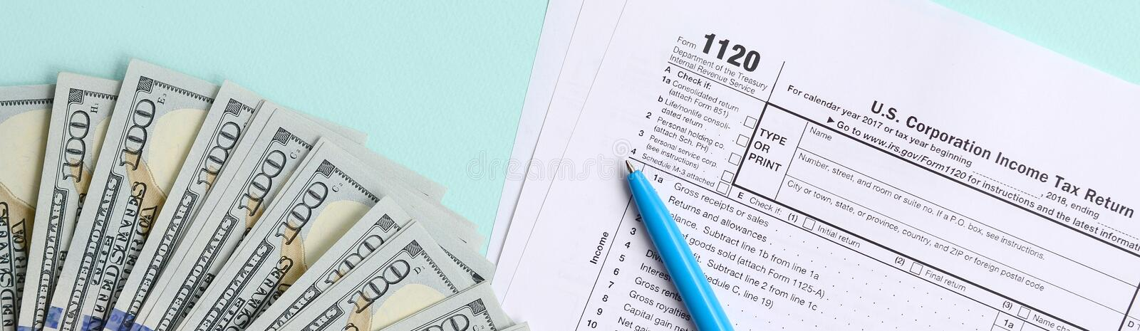 1120 tax form lies near hundred dollar bills and blue pen on a light blue background. US Corporation income tax return.  stock photo