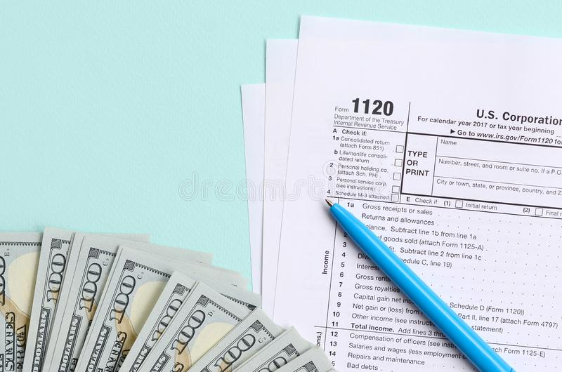 1120 tax form lies near hundred dollar bills and blue pen on a light blue background. US Corporation income tax return.  stock photos