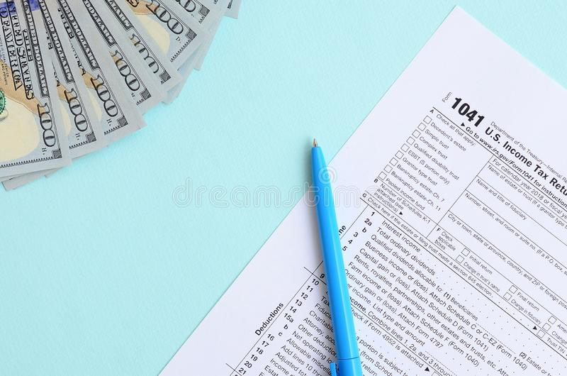 1041 tax form lies near hundred dollar bills and blue pen on a light blue background. US Income tax return for estates and trusts.  royalty free stock images