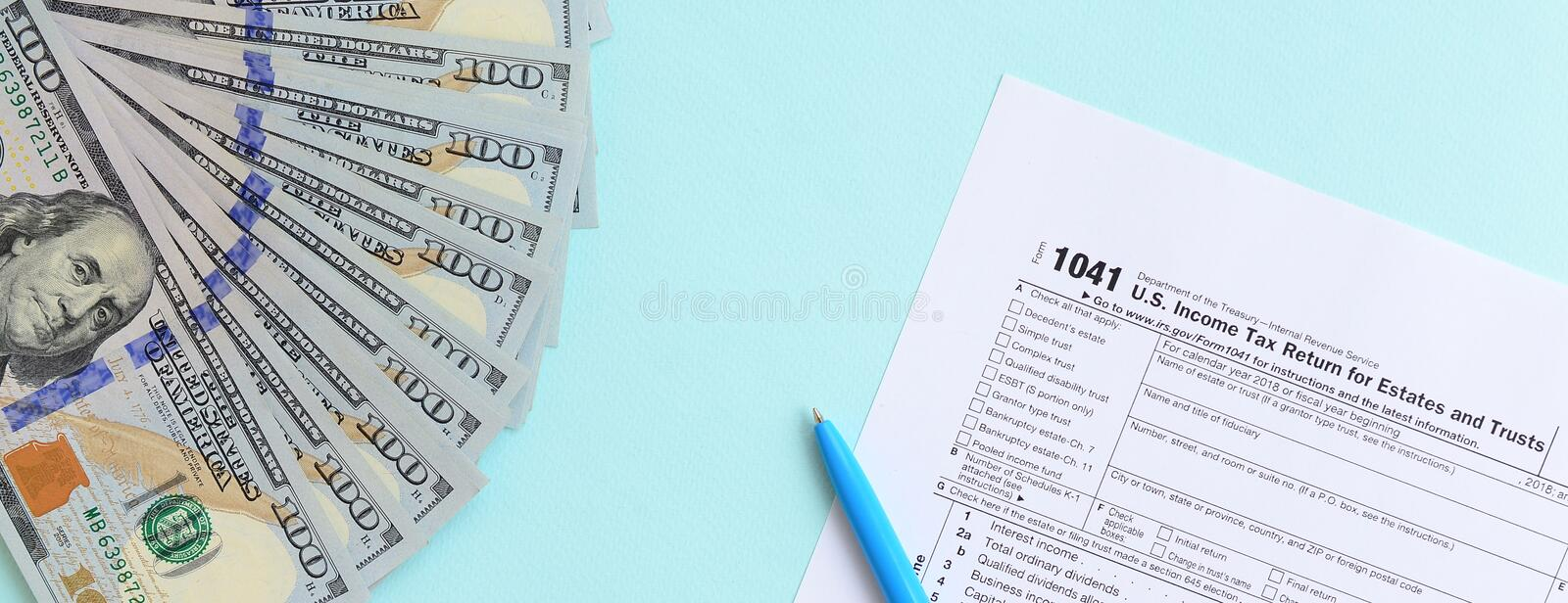 1041 tax form lies near hundred dollar bills and blue pen on a light blue background. US Income tax return for estates and trusts.  royalty free stock image