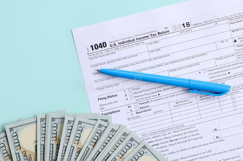 1040 tax form lies near hundred dollar bills and blue pen on a light blue background. US Individual income tax return.  stock photography