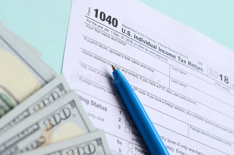 1040 tax form lies near hundred dollar bills and blue pen on a light blue background. US Individual income tax return.  stock photos
