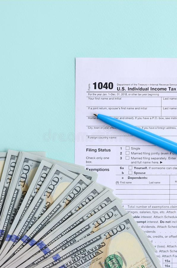 1040 tax form lies near hundred dollar bills and blue pen on a light blue background. US Individual income tax return.  royalty free stock photos