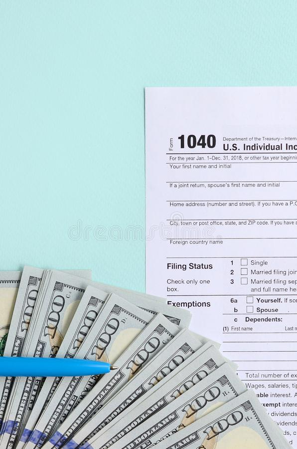 1040 tax form lies near hundred dollar bills and blue pen on a light blue background. US Individual income tax return.  royalty free stock photography