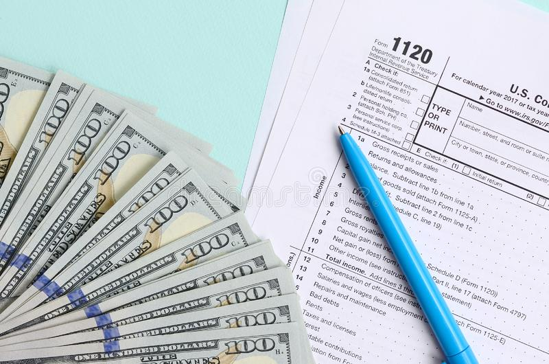 1120 tax form lies near hundred dollar bills and blue pen on a light blue background. US Corporation income tax return.  stock image