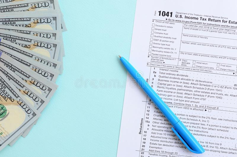 1041 tax form lies near hundred dollar bills and blue pen on a light blue background. US Income tax return for estates and trusts.  stock photo