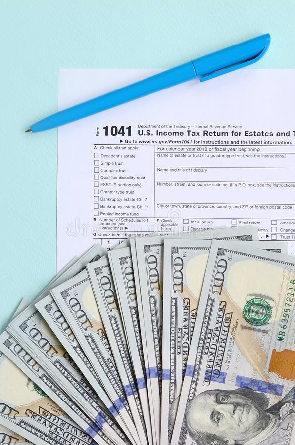 1041 tax form lies near hundred dollar bills and blue pen on a light blue background. US Income tax return for estates and trusts.  royalty free stock photography