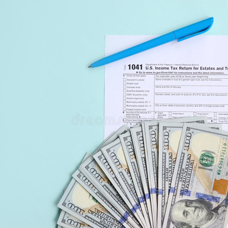 1041 tax form lies near hundred dollar bills and blue pen on a light blue background. US Income tax return for estates and trusts.  stock image