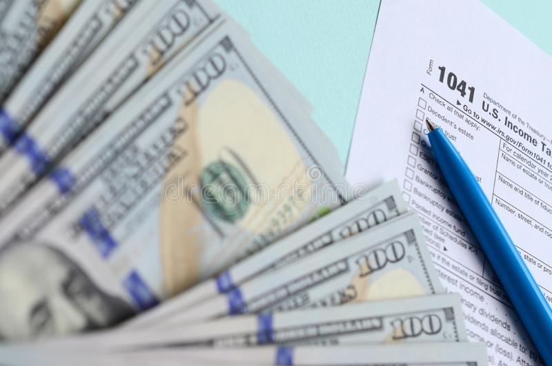 1041 tax form lies near hundred dollar bills and blue pen on a light blue background. US Income tax return for estates and trusts.  stock photos