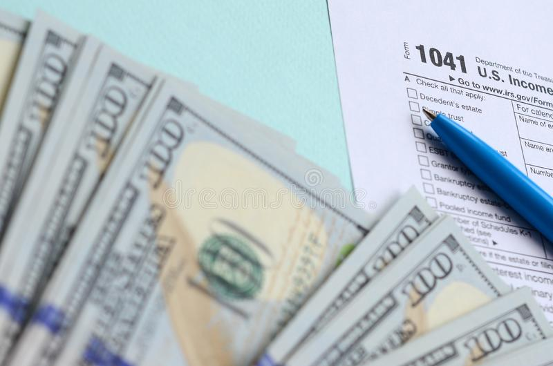 1041 tax form lies near hundred dollar bills and blue pen on a light blue background. US Income tax return for estates and trusts stock photography