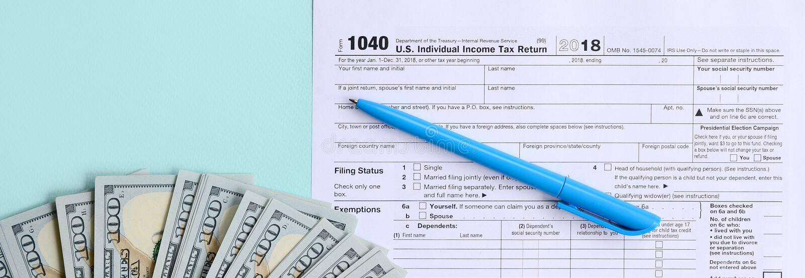 1040 tax form lies near hundred dollar bills and blue pen on a light blue background. US Individual income tax return stock image