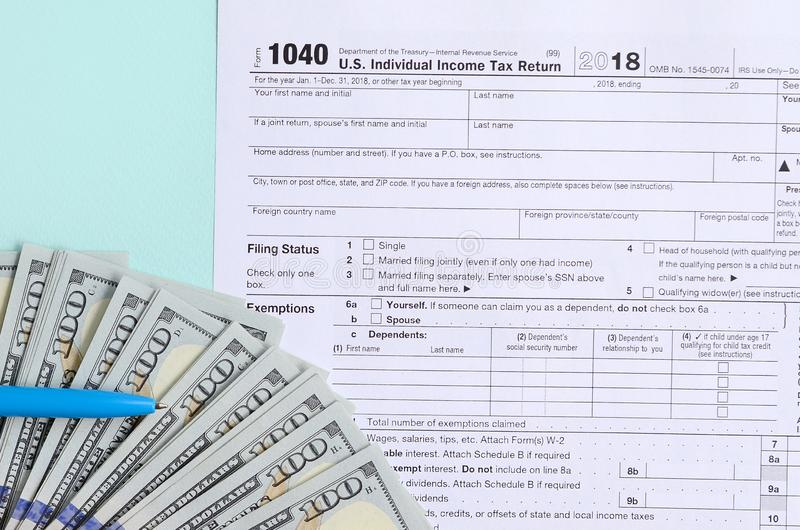 1040 tax form lies near hundred dollar bills and blue pen on a light blue background. US Individual income tax return.  stock photo
