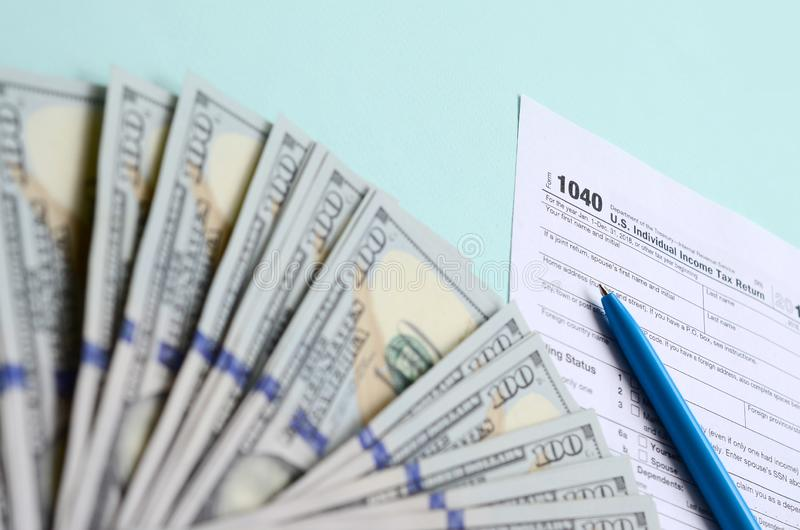 1040 tax form lies near hundred dollar bills and blue pen on a light blue background. US Individual income tax return.  stock image