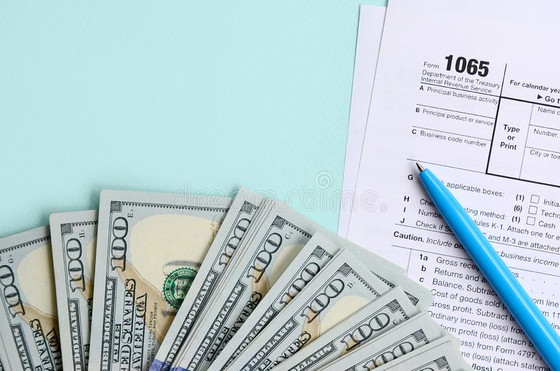 1065 tax form lies near hundred dollar bills and blue pen on a light blue background. US Return for parentship income.  stock images