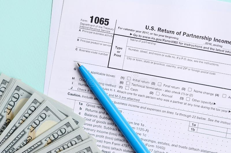 1065 tax form lies near hundred dollar bills and blue pen on a light blue background. US Return for parentship income.  stock photography
