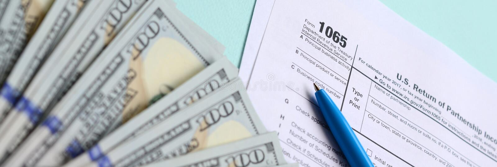 1065 tax form lies near hundred dollar bills and blue pen on a light blue background. US Return for parentship income.  royalty free stock photo