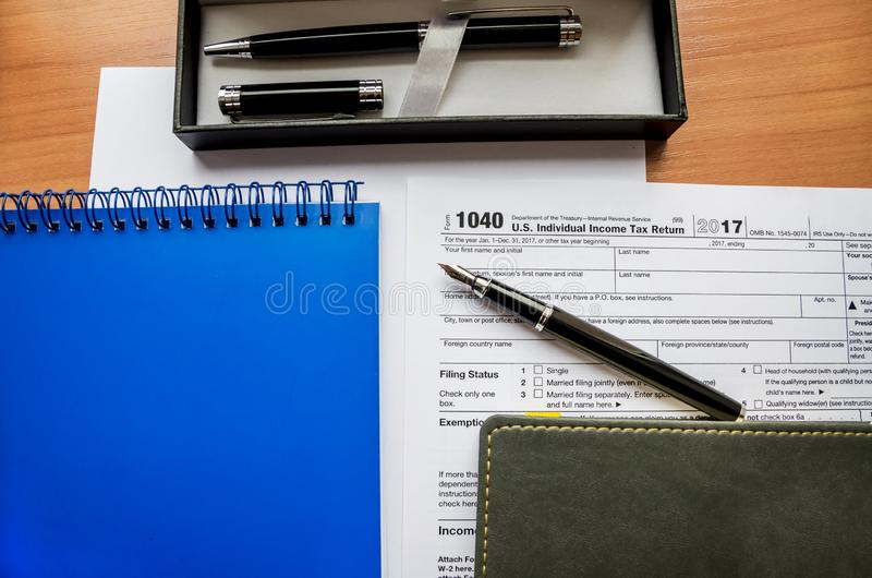 1040 tax form, notebooks and pens stock photos