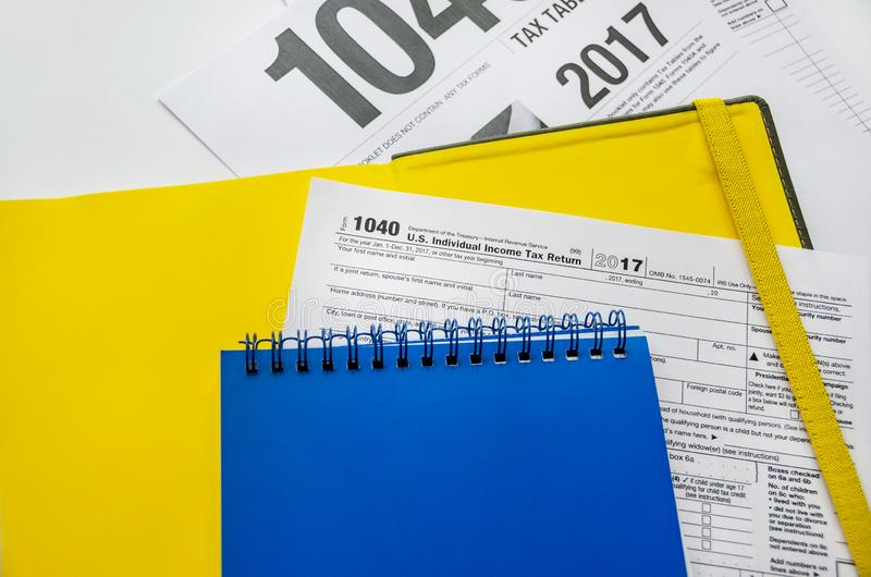 Tax form 1040 and notepads on white. Tax form 1040 and yellow and blue notebooks on a white background royalty free stock photo