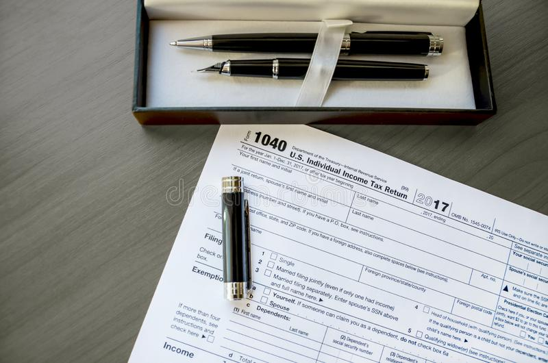 Tax form 1040, pens on a wooden table. Tax form 1040, pens and a case on a wooden table royalty free stock photography