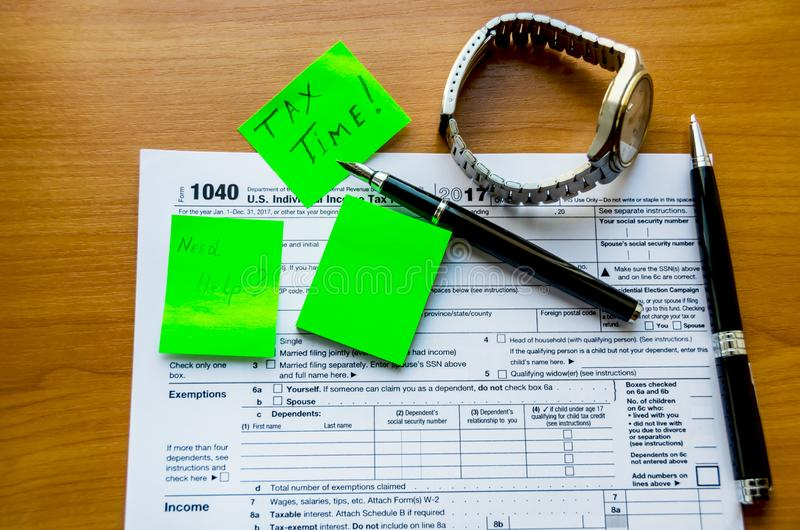 Tax form 1040, pens and watche on the table. Tax form 1040 and pens on a wooden table royalty free stock images