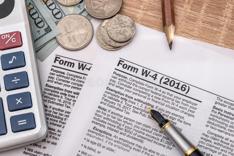Tax form w4 with pen and us dollar, calculator and pen.  stock photography