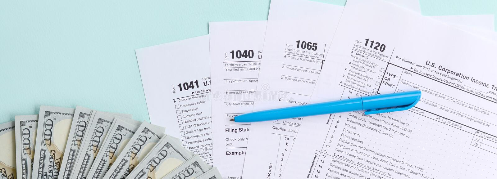 Tax forms lies near hundred dollar bills and blue pen on a light blue background. Income tax return royalty free stock photography