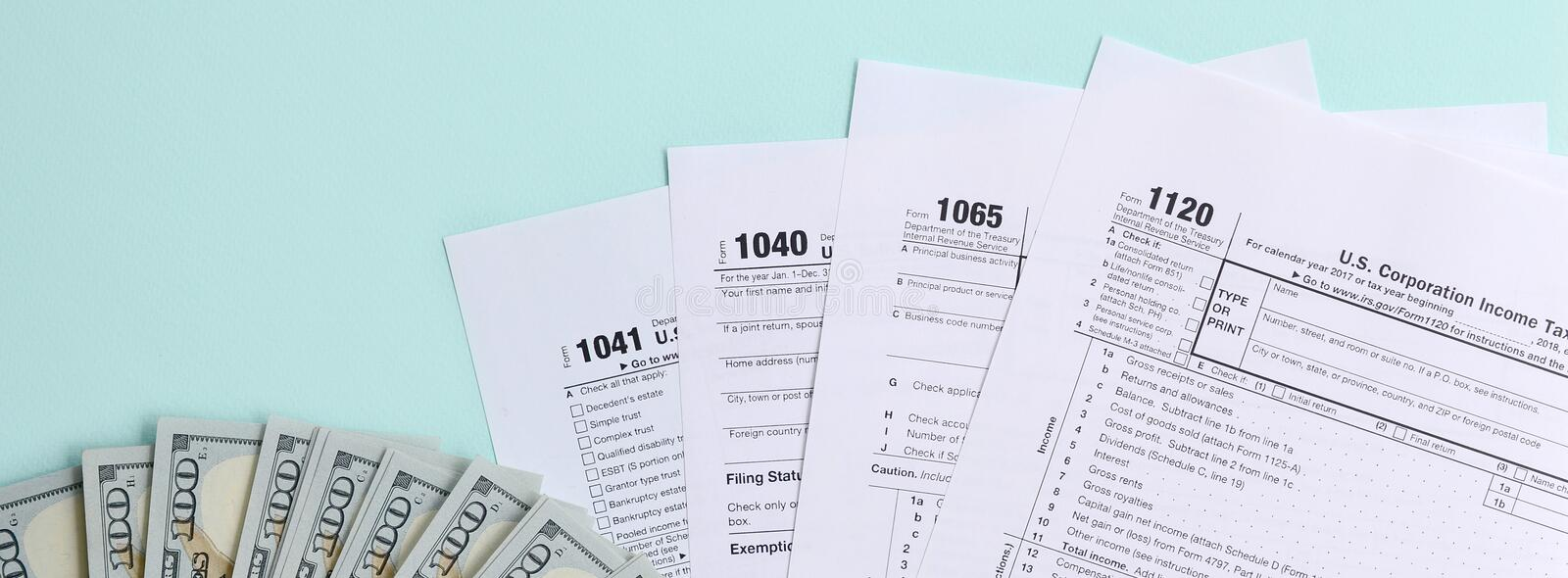 Tax forms lies near hundred dollar bills and blue pen on a light blue background. Income tax return stock photo
