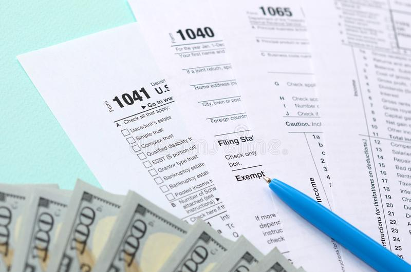 Tax forms lies near hundred dollar bills and blue pen on a light blue background. Income tax return stock photos