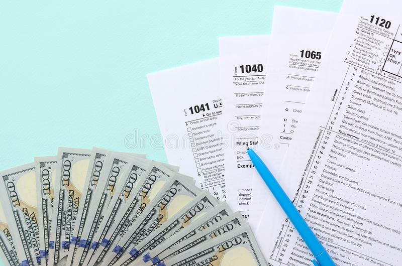 Tax forms lies near hundred dollar bills and blue pen on a light blue background. Income tax return royalty free stock image
