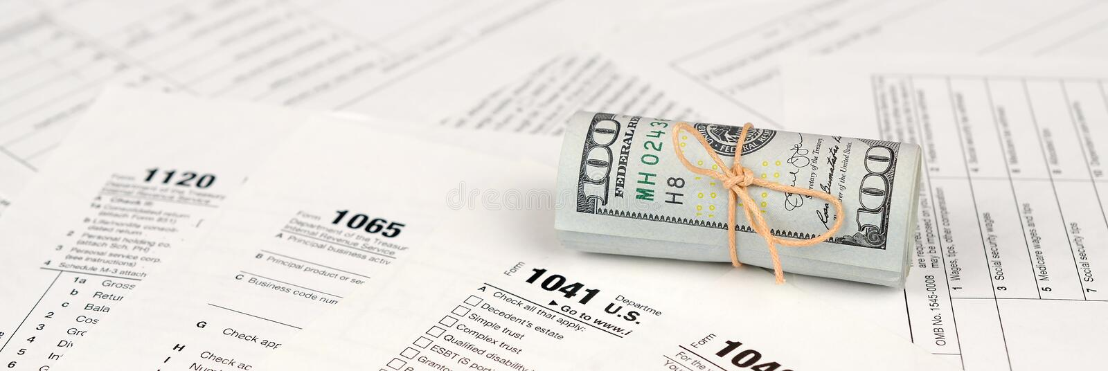 Tax forms lies near roll of hundred dollar bills. Income tax return. Time to pay taxes concept. 1040 1041 1120 and 1065 empty blank forms royalty free stock image