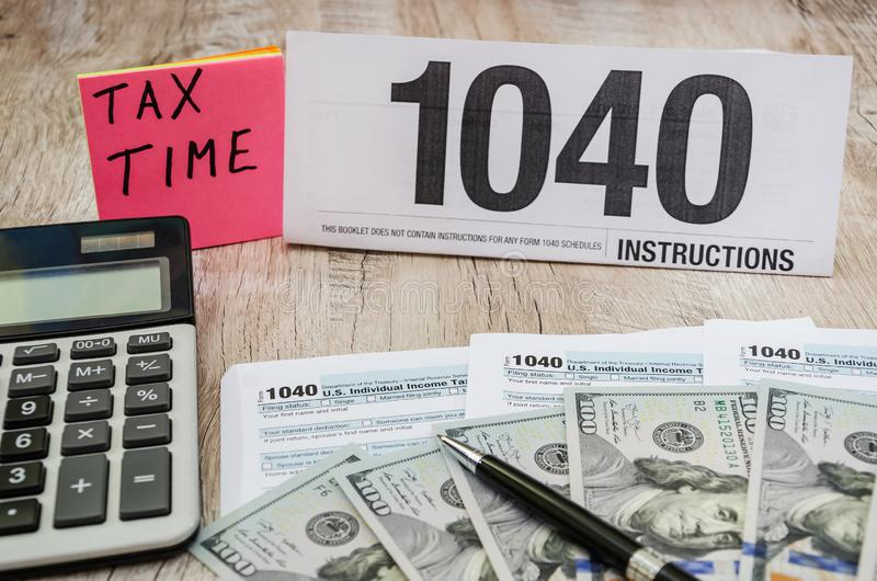 Tax forms 1040, dollars, calculator, pen on a wooden table. Tax forms 1040 on a wooden table stock photography