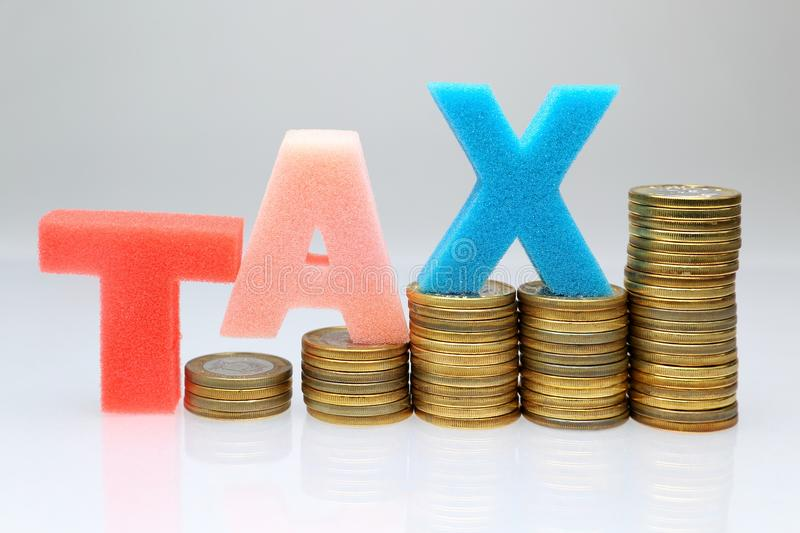 Tax increased. Tax word spelled out on stacks of gold coins . Concept for tax increase . on a white/gray background royalty free stock image