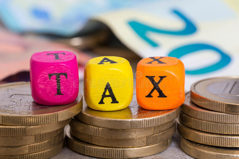TAX letter cubes on coins concept stock photography