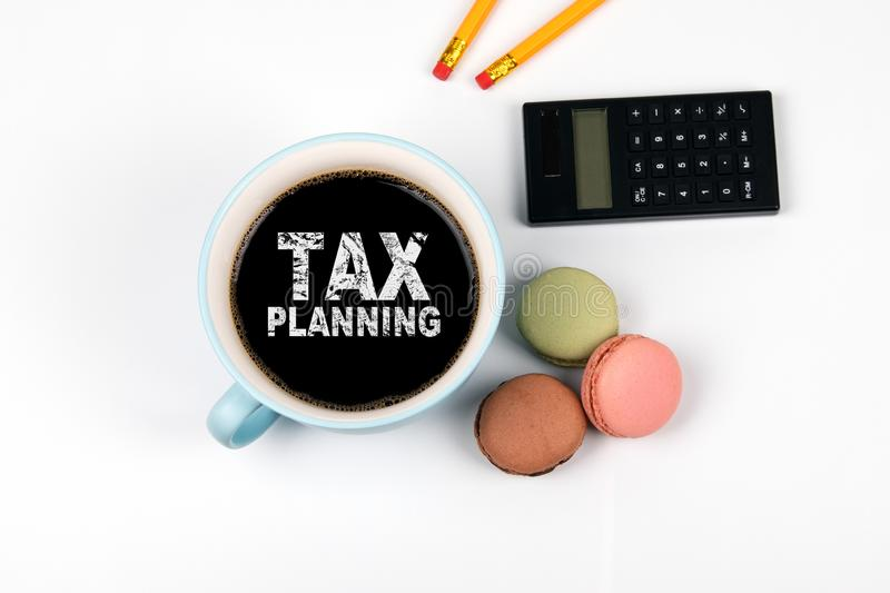 Tax planning. calculator with a cup of coffee and sweets. On a white table stock image