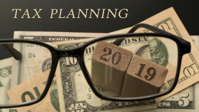 Tax planning concept. Glasses, number 2019, Tax planning words. Dollar banknotes background. 16:9 format. Selective focus royalty free stock photo