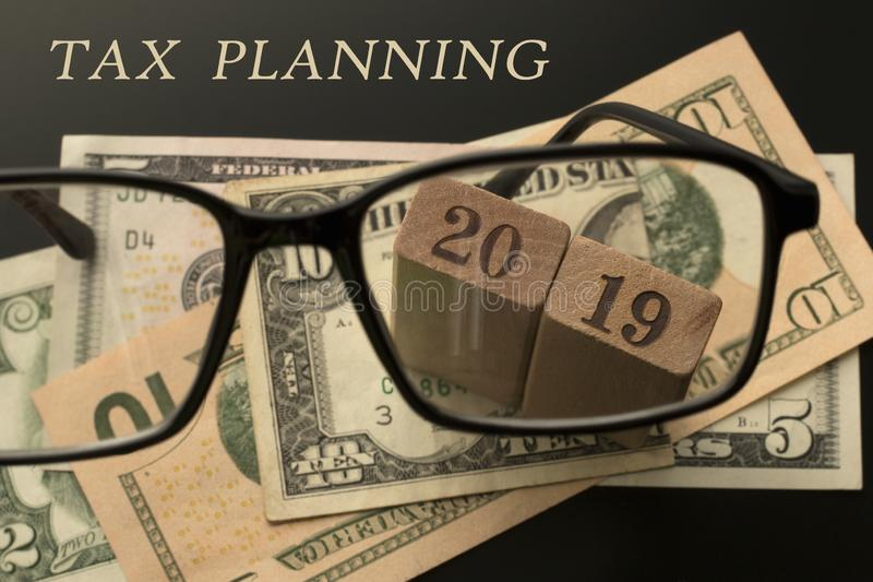 Tax planning concept. Glasses, tax planning 2019 text, dollar banknotes background royalty free stock photography