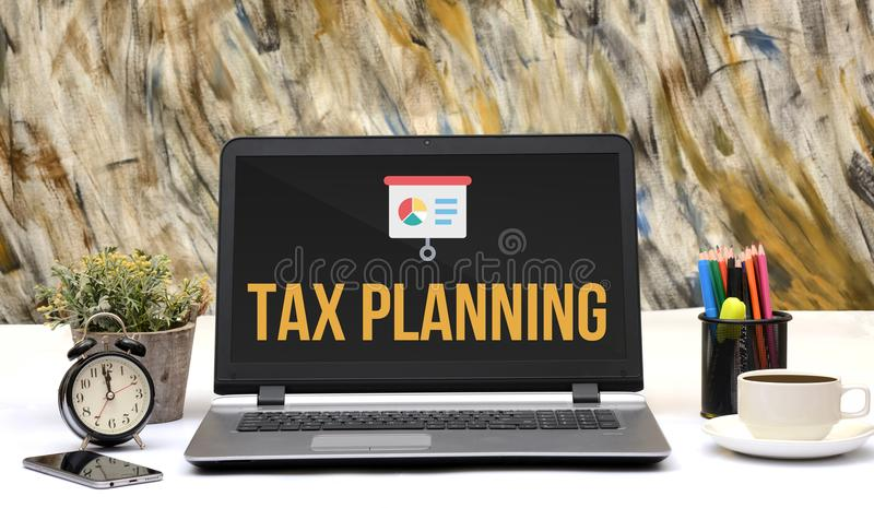 Tax Planning icon on laptop screen in office.  royalty free stock photos