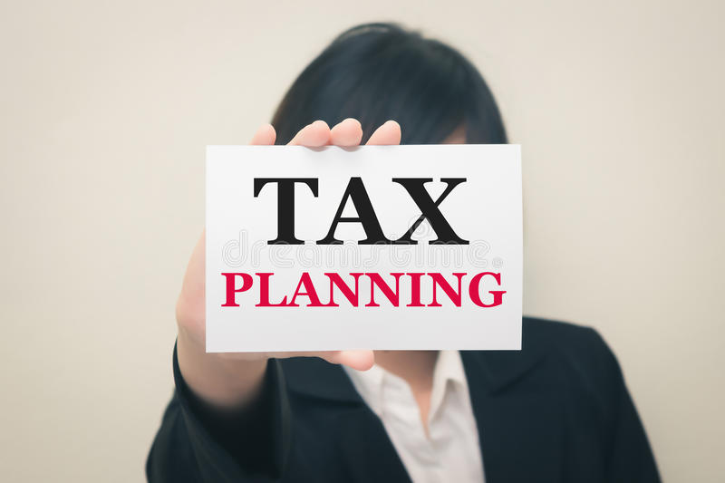 TAX PLANNING, message on the card Held by women. Vintage tone royalty free stock image