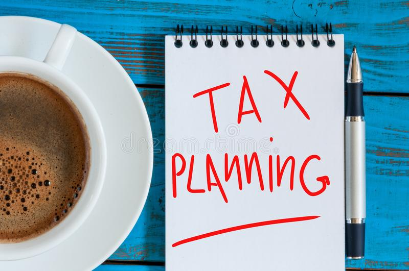 Tax planning, reminder with red ink in the diary near morning coffee cup. top view.  stock photo