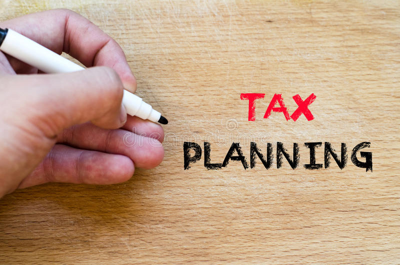 Tax planning text concept. Human hand over wooden background and tax planning text concept royalty free stock photography