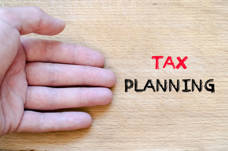 Tax planning text concept. Human hand over wooden background and tax planning text concept stock photo