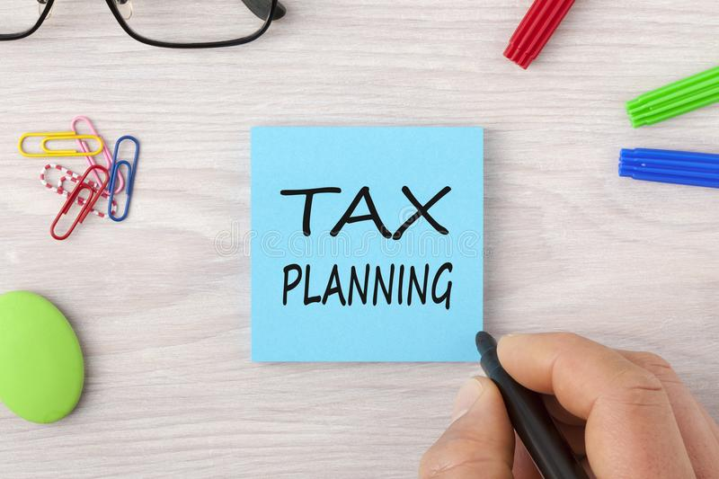 Tax Planning writing on note concept. Hand writing TAX PLANNING in note with marker pen and glasses on wooden desk. Business Concept. Top view royalty free stock photo